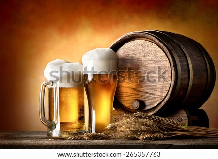 Beer with wheat and barrel on a wooden table - stock photo