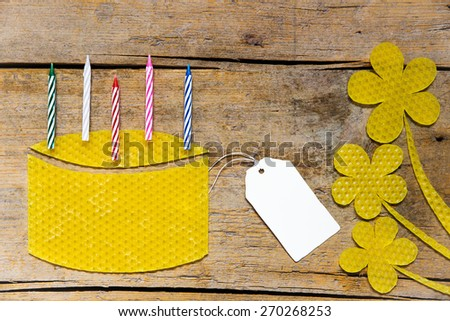 Beeswax cake with flowers and blank sign - stock photo