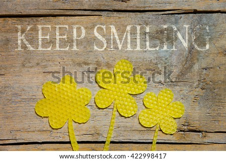 beeswax, three flowers on wooden table, text keep smiling - stock photo
