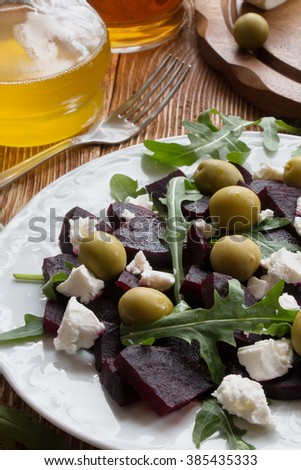 Beet (beetroot) salad with cheese, olives and arugula on the white plate. Olive oil and lemon dressing. On the wooden table. - stock photo