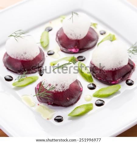 Beet root salad with asparagus on white plate - stock photo