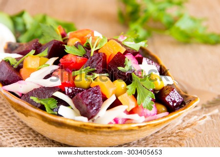 Beet salad. Russian beetroot salad (vinegrette) with beetroot, potato, carrot, peas, cabbage and parsley over rustic wooden table. - stock photo