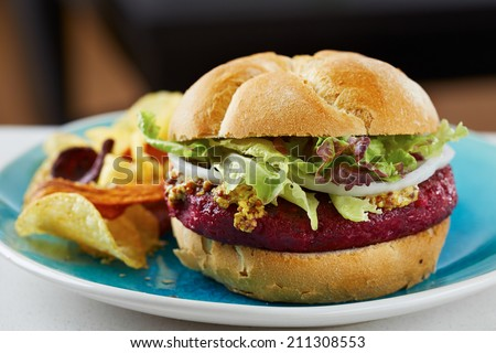 Beetroot burger on white bread with chips - stock photo