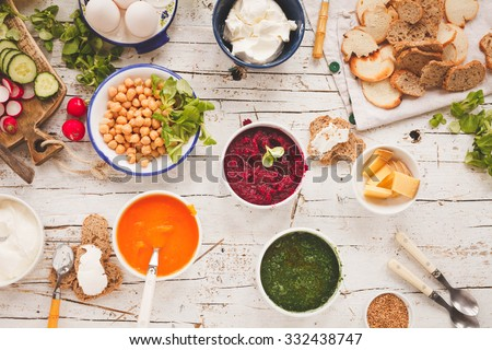 Beetroot, carrot, pumpkin, spinach dip in white cookware with various fresh vegetables, bowl with cooked chickpeas, cream cheese and slicing bread from above white rustic table. - stock photo