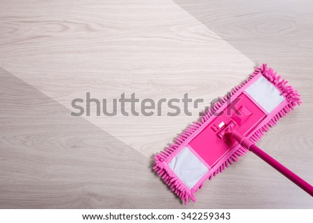 before and after cleaning concept - close up of pink floor mop on wooden background - stock photo