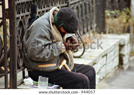 beggar counting his proceeds, soft focus and snow noise - stock photo