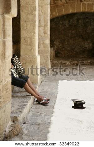 Beggar hidden accordion musician with hat on floor on Ibiza castle - stock photo
