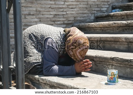 Beggar in Rome - female street beggar in prayer pose - stock photo