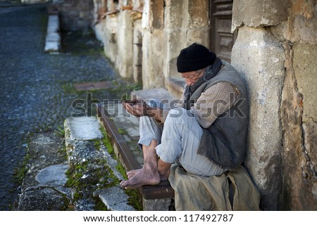 Beggar is begging for food on the street - stock photo