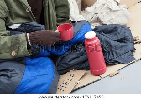 Beggar warming himself by a hot tea  - stock photo