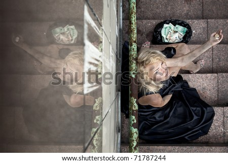 beggar woman is sitting on the step subway and looking up - stock photo