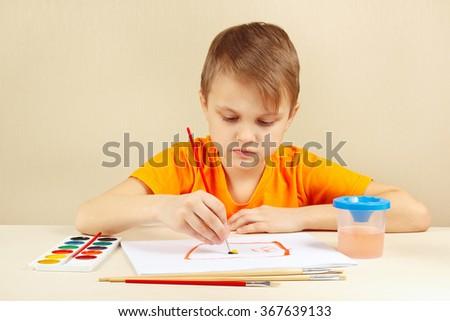 Beginner artist in an orange shirt painting colors - stock photo