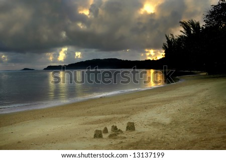 Beginning of a new day on the beach in paradise.  Remnant of the previous day's sand castle still stands.  Large cloud cover with gold peeking through. - stock photo