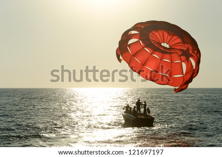 Beginning of flight with a parachute behind a boat - stock photo