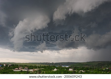 Beginning of the storm with small tornado above the village - stock photo