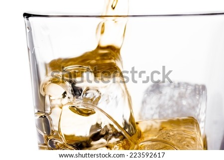 beginning pouring scotch whiskey in glass with ice cubes isolated on white background - stock photo