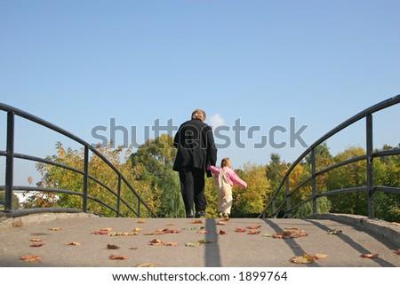 behind grandmother and baby on autumn bridge - stock photo