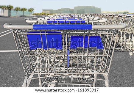 Behind rows of stacked empty shopping carts in parking lot.Rear view close up.Metal wire cart, blue handle.White painted lines on grey pavement.Cyan sky.Commercial buildings,palm trees in background.  - stock photo