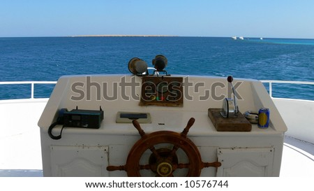 Behind the wheel - captain's bridge on a boat - stock photo