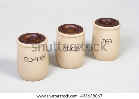 Beige and Brown Tea, coffee and sugar cannisters set  with wooden cap on a gray background - stock photo