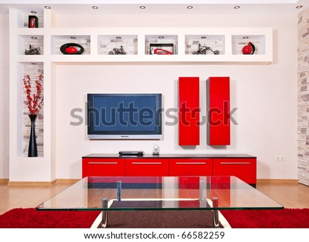 Beige and red interior of modern house with flat TV set - stock photo