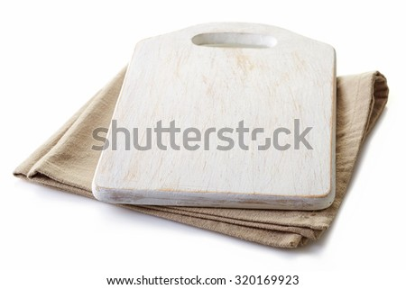 Beige cotton napkin under a white cutting board isolated on white background - stock photo