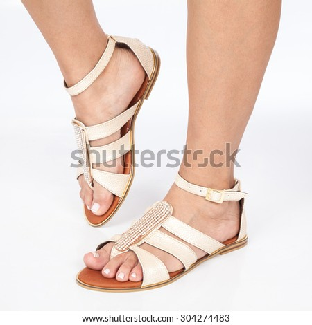 beige leather sandals with gold applied on feet the women's on white background - stock photo