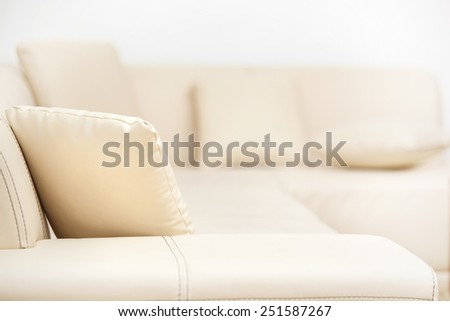 Beige leather sofa with pillows in the living room - stock photo