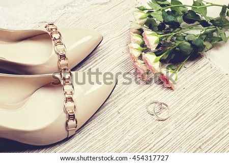 Beige patent leather shoes with gold buckle, two wedding rings of white gold and sprig of delicate pink roses on the table.  Concept of wedding fashion, beauty and wedding ceremony. - stock photo