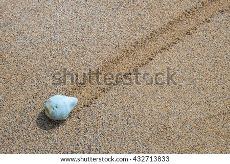 Beige stone at right side of sand background, pebbles on a sandy beach - stock photo