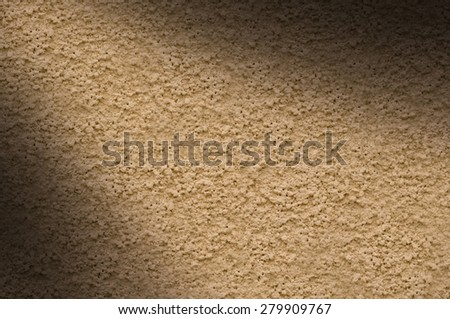 Beige stucco wall texture lit diagonally from left - stock photo