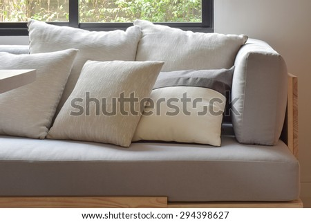 Beige varies size pillows setting on light gray comfy sofa - stock photo