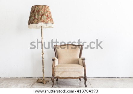 Beige vintage armchair and lamp on white wall. - stock photo