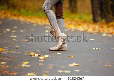Beige women's boots in the autumn road with yellow leaves in autumn - stock photo