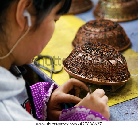 BEIJING - April 11, 2016: An artisan in China Making Cloisonne. Cloisonne have originated in Beijing during Yuan Dynasty.  - stock photo