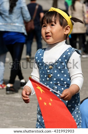 BEIJING - April 09, 2016 : Chinese girl holding Chinese flag - stock photo