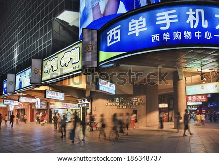 BEIJING-APRIL 24, 2013. Shoppers at Xidan Shopping Center at night. The 3,4 miles long Xidan shopping street is very popular among Beijingers, it offers many shops, shopping malls and entertainment. - stock photo