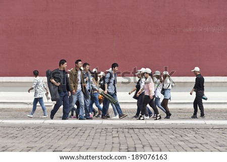 BEIJING-APRIL 14, 2014. Tourists on a walkway in Palace Museum. The world's largest palace complex has more than 8,700 rooms, covers 74 hectares, is surrounded by 52m wide moat and a 10m high wall. - stock photo