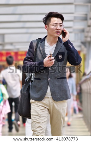 BEIJING-APRIL 28, 2016. Young man with two smartphones. China mobile internet market will exceed US$717 billion in 2016 with 830 million users, in 2018: 7,654 US$1,175 billion and 890 million users. - stock photo