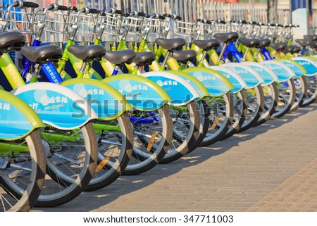 BEIJING-AUG. 27, 2015. Bicycles parked in public bicycle sharing station. Bicycle sharing allow to hire on a very short term basis, a popular transport mode among commuters in major Chinese cities. - stock photo