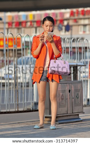 BEIJING-AUGUST 27, 2015. Girl busy with smart phone on the street. China has currently 519.7 million smartphone users. Figure has raised to 574.2 million Chinese smartphone users by the end of 2015. - stock photo