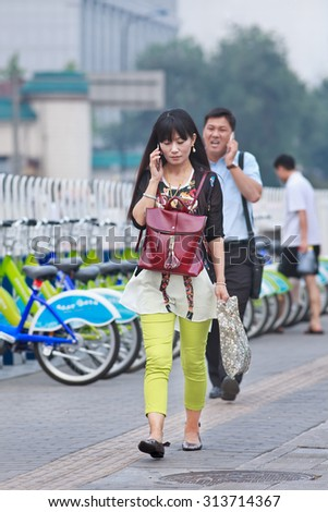 BEIJING-AUGUST 5, 2015. Woman walks on the street while calling. China has currently 519.7 million smartphone users. Figure has raised to 574.2 million Chinese smartphone users by the end of 2015. - stock photo