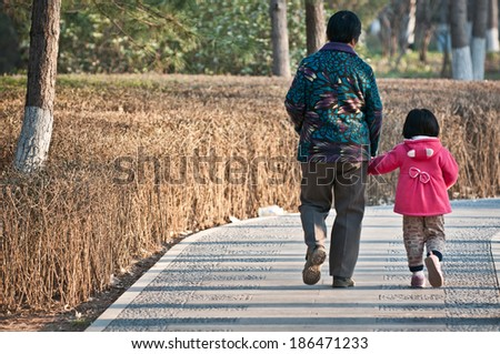 Beijing, China - April 1st, 2013: old Chinese woman walks with her granddaughter walking on a pavement in small park on April 1, 2013 in Beijing - stock photo