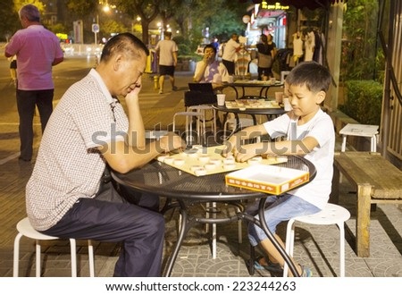 Beijing, China - August 4, 2014: A father is playing traditional Chinese game with his son in front of a restaurant in Beijing. - stock photo