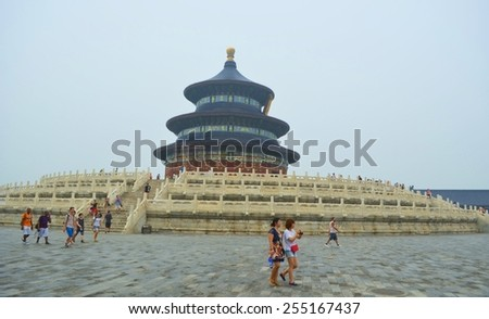 BEIJING, CHINA, AUGUST 15, 2013: Group of people is passing in front of the giant pagoda inside the temple of heaven complex in beijing. - stock photo