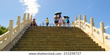 BEIJING, CHINA, AUGUST 15, 2013: People are crossing bridge on the kunming lake inside of the new summer palace complex in chinese capital beijing. - stock photo