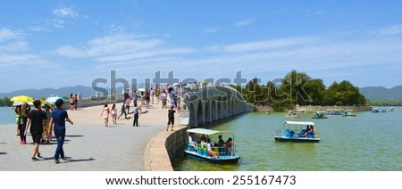 BEIJING, CHINA, AUGUST 15, 2013: People are walking over famous 17 arch bridge inside of the new summer palace complex in chinese capital beijing. - stock photo