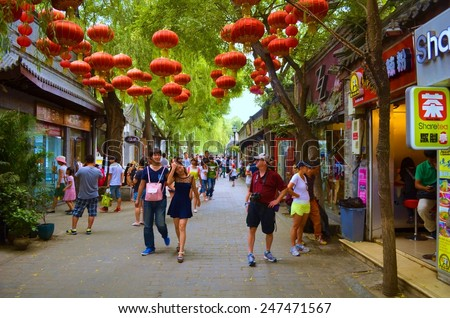 BEIJING, CHINA, AUGUST 20, 2013: people are walking through tourist street in hutong quarter of beijing. - stock photo