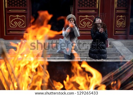 BEIJING, CHINA - CIRCA JANUARY 2013: Unidentified women praying in the Lama Temple on circa January 2013 in Beijing, China. It is one of the largest and most important Tibetan Buddhist monasteries in the world. - stock photo