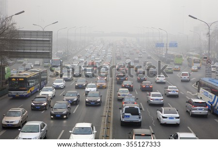 BEIJING, CHINA - DECEMBER 25, 2015: Traffic is seen at Guomao area in heavy smog. Today more than 200 flights were cancelled at the Beijing International Airport as heavy smog shrouded the city. - stock photo